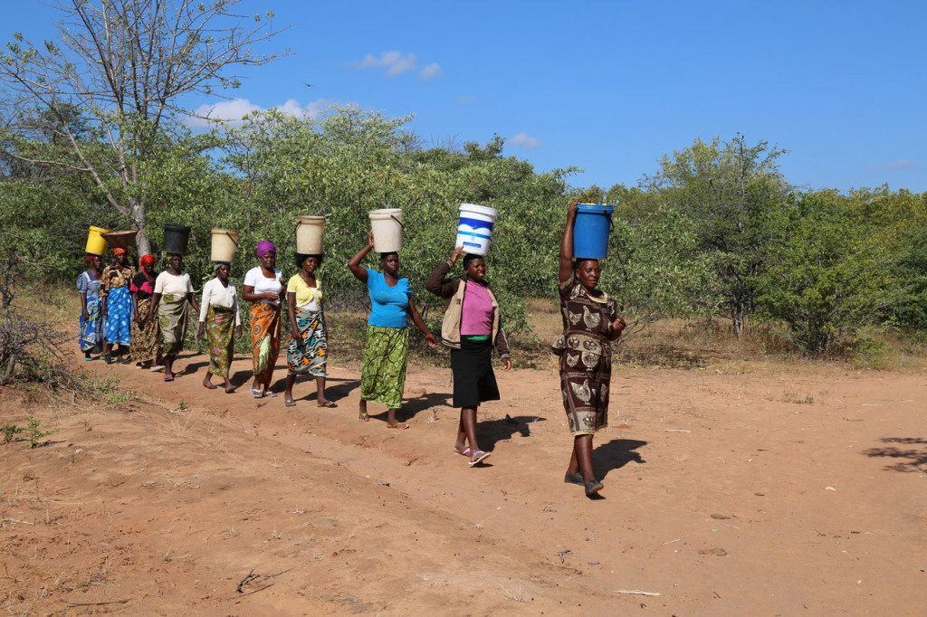 line of women carrying goods on their heads